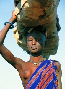 At the end of the dry season when pastures are scarce, the dinka return with their cattle to their village homesteads on higher ground.women carry all of their possessions balanced on their heads, while men drive the herds.